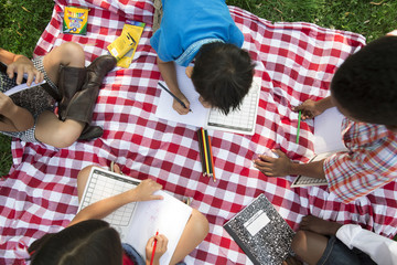 Overhead view of children drawing while sitting on blanket