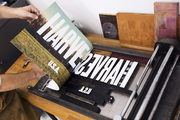 Close-up of craftsperson taking picture off letterpress