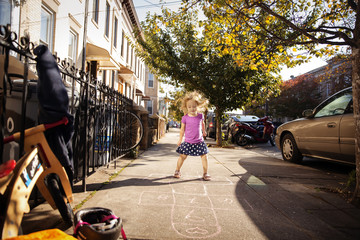 Girl playing hopscotch on footpath