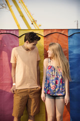 Happy couple standing against multi colored metallic wall at amusement park