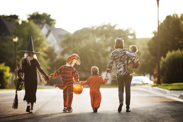 Rear view of a family dressed up in costume for Halloween Wall mural
