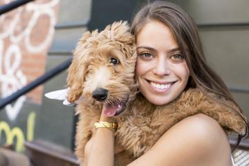 Portrait of woman embracing poodle