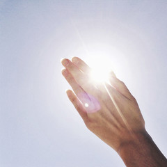 Woman's hand against sky in sunny day