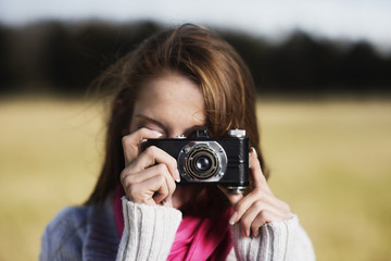 Close-up of woman wearing sweater photographing through camera at field