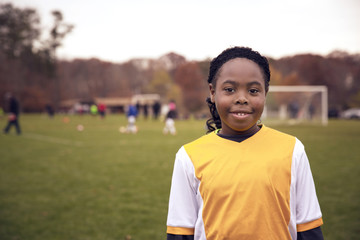 Portrait of smiling soccer player standing on field
