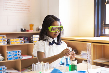 Schoolgirl performing science experiment in laboratory