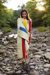 Young woman wrapped in blanket standing on rocky riverbank