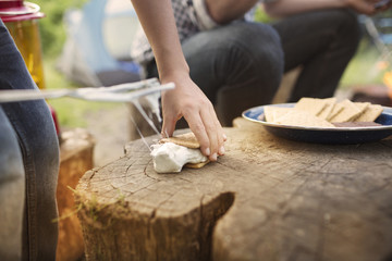 Cropped image of hands preparing smores during summer camp