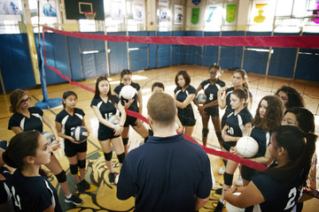 Instructor guiding volleyball players in court