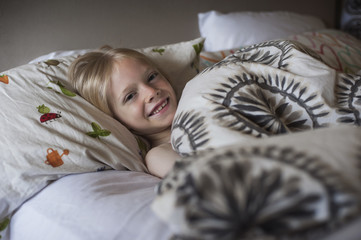 Smiling boy lying in bed