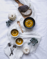 Overhead view of soup served in bowls with pumpkins and breads on textile