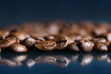Coffee beans on a black background. Raw coffee beans. Grained product. Hot drink. Close up. Harvesting. Natural background. Energy. Reflection in a glass