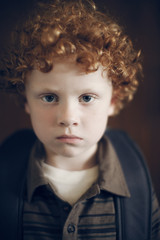 Portrait of red haired boy with curly hair