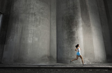 Young woman running along railroad track