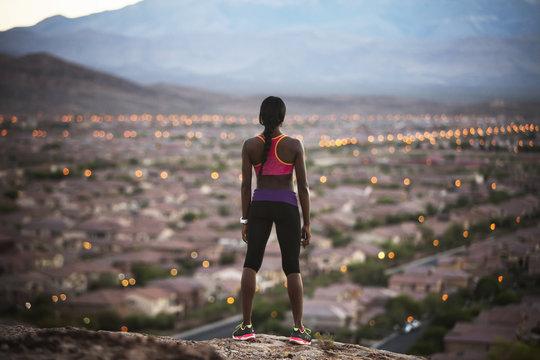 Woman looking at suburb at dusk,