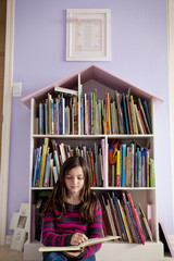 Girl reading book while sitting in bedroom