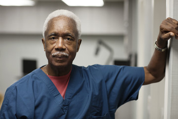 Portrait of doctor standing by wall in hospital