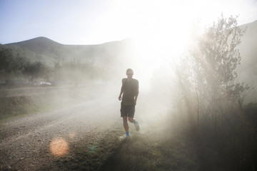 Young man in dust on sunlit country road