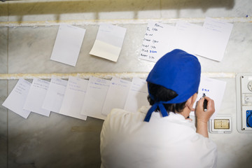 Rear view of butcher writing orders on notes at shop