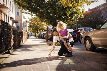 Father carrying daughter while drawing hopscotch on footpath