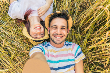 Young caucasian couple taking selfie lying on the grass.