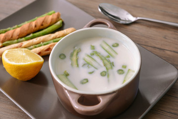 Asparagus soup with lemon and bread sticks on wooden table