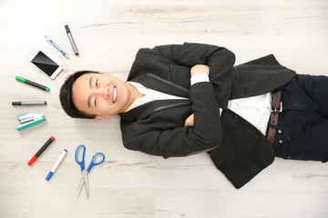 Handsome businessman with office supplies lying on floor
