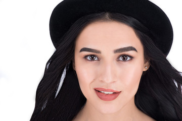 Closeup headshot of a stylish beautiful girl in black hat over white background