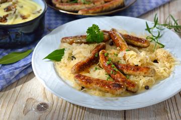 Deftige, gebratene Rostbratwürstchen auf Sauerkraut mit Kartoffelpüree serviert - Fried Bavarian sausages from Nuremberg on sauerkraut served with mashed potatoes