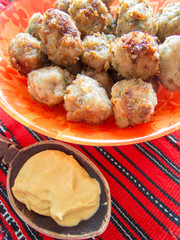 Fototapete - fried meatballs on a plate with a wooden spoon with mustard