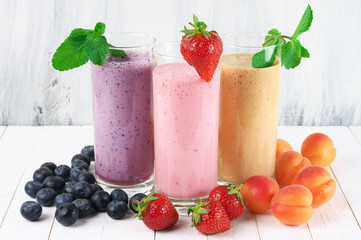 Three various protein milkshakes in glasses with fruits on rustic white wooden background.