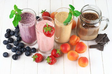 Various fruit and chocolate protein milkshakes in glasses on rustic white wooden background. Overhead view.