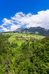 Summer view of Sigriswil village with Emmental Alps in the background