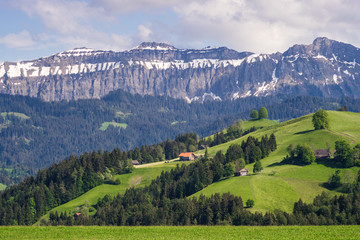 Summer landscape in Berner Oberland region of Switzerland. Green meadows, farmhouses and mountains.
