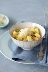 Colorful gnocchi trio (potato, spinach and tomato) with cream sauce and grated parmesan. Selective focus.