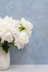 Bouquet of white peonies in ceramic vase against gray-blue venetian stucco wall. Selective focus on the flowers.