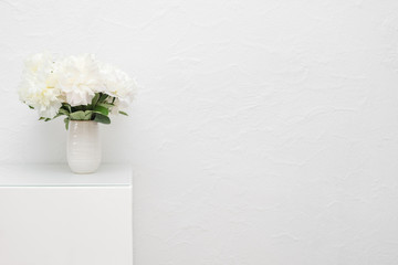 Bouquet of white peonies in ceramic vase against white stucco wall. Selective focus on the flowers.