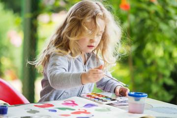 Portrait of little blonde girl painting, summer outdoor