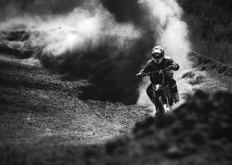 Motocross racer przyspieszający na torze pyłu, czarno-białe zdjęcie - 113262378