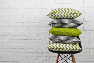 Colorful pillows on chair, on white bricks wall background