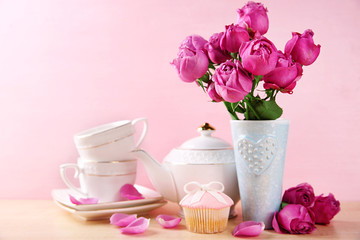 Mother Day concept. Roses with tableware on pink background