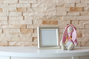 Baby toy and frame on brick wall background