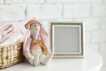 Baby toy and clothes on brick wall background