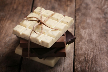 Different chocolate bars on wooden background