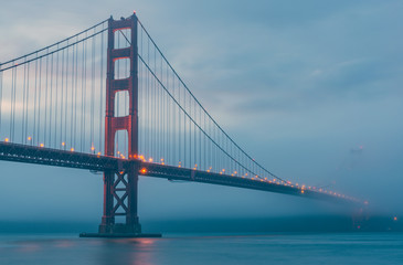 scenic view of Golden gate in the in the dusk with lighting and fog.