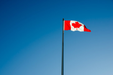 Poster Canada Canadian flag waving over blue sky