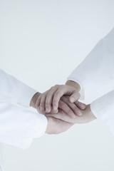手を重ねる2人の医師