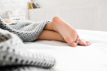 Sleeping woman feet under blanket. Beautiful feet of sleeping woman under the blanket on her bed. Bedroom on background. Focus on beautiful feet. Free space
