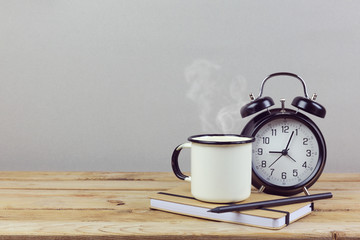 Coffee cup and alarm clock on wooden table