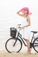 beautiful woman having fun and smiling riding bicycle on the bea